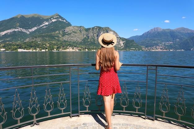 Vacanze sul lago di como. vista posteriore della bella ragazza di moda che gode della vista del lago di como dal lungomare di bellagio. vacanze estive in italia.