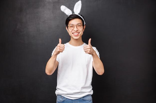 Concetto di vacanze, feste e pasqua. il ritratto di un giovane ragazzo asiatico carino e divertente nelle orecchie di coniglio consiglia qualcosa, dà buoni consigli, garantisce lo spettacolo di qualità pollice in su e sorride felice