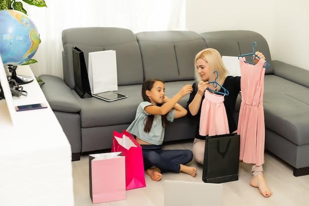 Vacanze, regali, natale, natale, concetto di compleanno - felice madre e bambina con sacchetti regalo