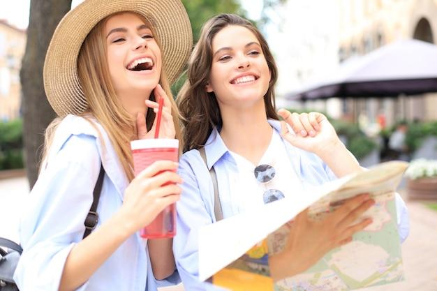 Vacanze e concetto di turismo - belle ragazze in cerca di direzione in città.