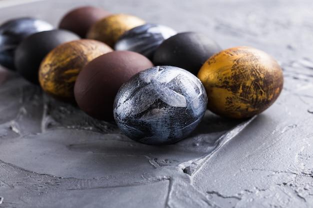 Feste, tradizioni e concetto di pasqua - uova di pasqua alla moda scure su fondo grigio.