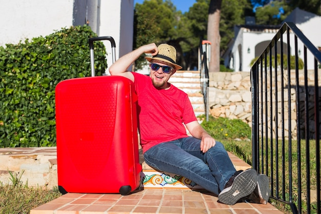 Vacanze, viaggi, concetto di persone. giovane uomo seduto sulle scale con le valigie.