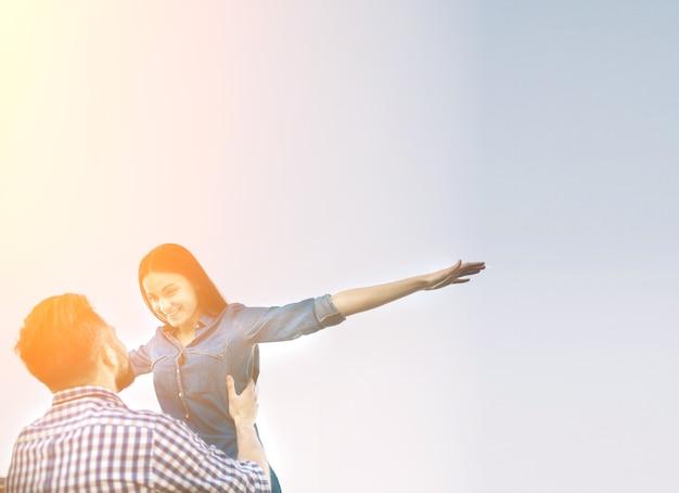 Vacanze, vacanze, amore e concetto di amicizia - coppia sorridente divertendosi sopra il fondo del cielo.