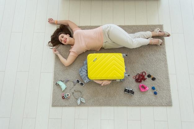 Vacanze, viaggio e concetto di persone - la giovane bella donna fa la valigia per un viaggio estivo, vista dall'alto