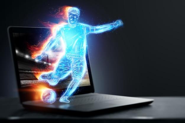 Un ologramma di un giocatore di calcio che sta finendo un notebook, lo schermo del laptop. il concetto di scommesse sportive, calcio, gioco d'azzardo, trasmissione online del calcio.