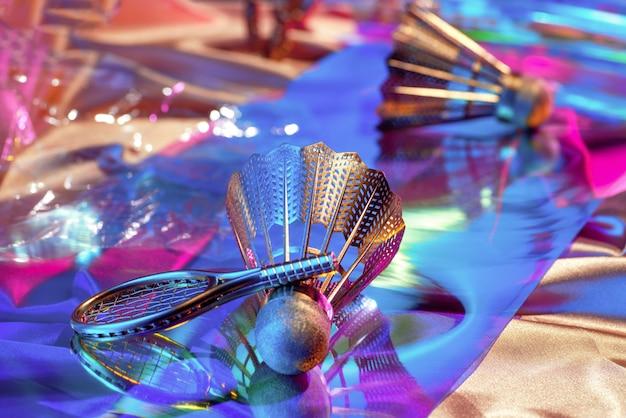Superficie di tessuti iridescenti arcobaleno olografico e oggetti degli anni '90: volano, racchetta, audiocassetta, retrospettiva anni '80, concept sportivo.