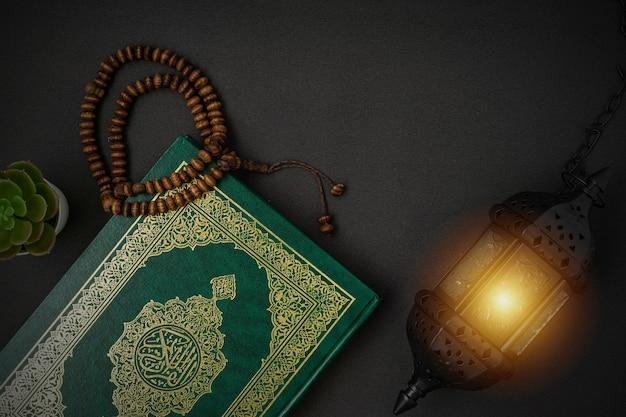 Sacro al quran con calligrafia araba scritta che significa al quran e grani del rosario su fondo nero