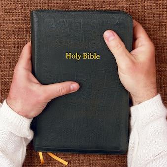 La sacra bibbia nelle mani dell'uomo