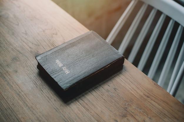 Sacra bibbia sullo sfondo della tavola in legno con morbida luce del sole mattutino. concetto di cristianesimo. concetto di amore di speranza di fede.