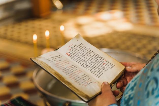 Libro sacro aperto nelle mani del sacerdote in chiesa