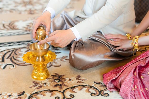 Cerimonia di versamento dell'acqua santa con le mani dello sposo e della sposa, fidanzamento di nozze tradizionale tailandese