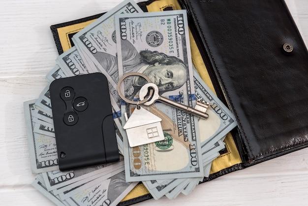 Chiavi della macchina di homa nad con banconote da un dollaro sul tavolo. concetto di risparmio