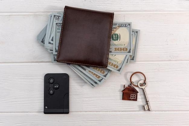 Homa nad chiavi della macchina con banconote da un dollaro sul tavolo. concetto di risparmio