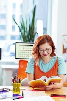 Compito per casa. donna felice e positiva che prepara il suo compito a casa mentre si prepara per le lezioni universitarie