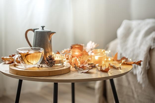 Composizione autunnale domestica con tè, foglie secche e candele accese su sfondo sfocato, spazio copia.