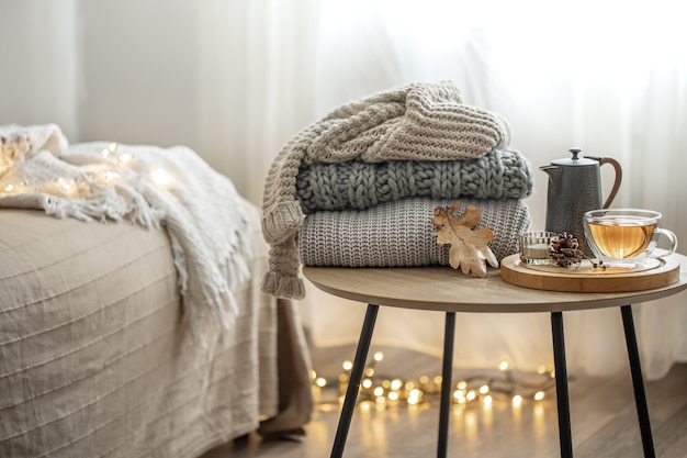 Composizione autunnale domestica con tè e maglioni lavorati a maglia all'interno della stanza, su uno sfondo sfocato.