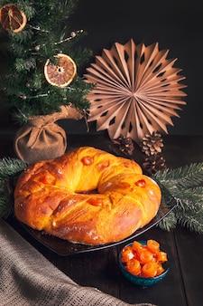 Pane di natale cotto in casa a forma di corona dell'avvento di pasta lievitata con frutta candita arancione su sfondo di albero di natale.