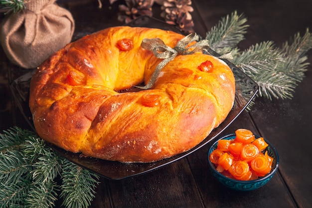 Pane di natale cotto in casa a forma di corona dell'avvento di pasta lievitata con frutta candita arancione su sfondo di rami di abete.