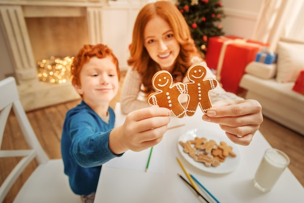 Bontà fatta in casa. fuoco selettivo sugli uomini di pan di zenzero tenuti da una famiglia allegra che sorride ampiamente mentre si riunisce a un tavolo e si gode il periodo natalizio a casa.