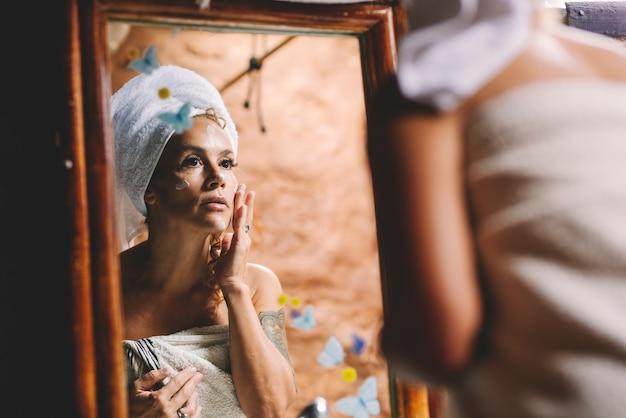 La cura di bellezza domestica fa la donna adulta che applica la crema per il viso anti età in bagno guardando uno specchio dopo la doccia. attività di persone sane di cura del corpo. femmina con asciugamano