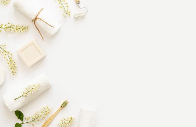 Elementi essenziali di bellezza domestica e concetto di cura di sé a casa. rami fioriti di ciliegia di uccello su baground bianco. candela bianca, sapone, crema, asciugamani. copia spazio. lay piatto.