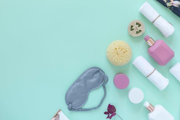 Elementi essenziali di bellezza domestici e trattamenti di auto-cura sfondo di menta disteso. copia spazio.