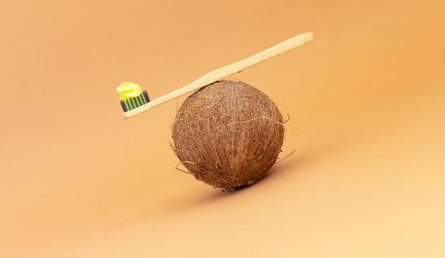 Elementi essenziali di bellezza per la casa. spazzolino da denti in legno con dentifricio verde naturale e cocco. copia spazio.