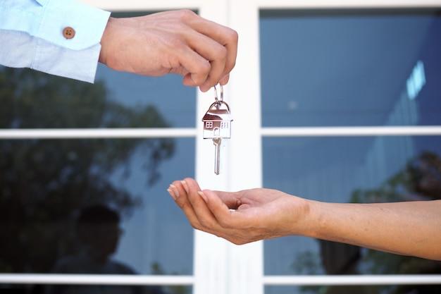 Gli acquirenti di case stanno prendendo le chiavi di casa dai venditori. vendi la tua casa, affitta casa e acquista idee.
