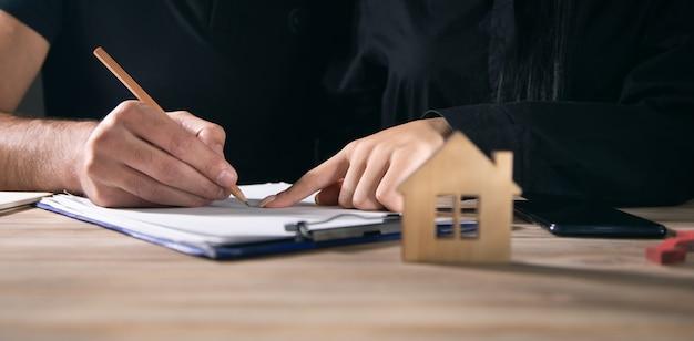 Gli acquirenti di case si incontrano e negoziano con gli agenti immobiliari.