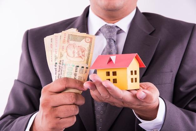 Concetto di acquisto di casa e auto, uomo indiano che tiene valuta indiana in entrambe le mani e casa modello e macchinina su di esso, primo piano e messa a fuoco selettiva