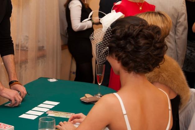 Casinò casalingo. uomini e donne giocano a carte. scommetti con denaro e fiches sui numeri. tovaglia verde da tavola. giochi d'azzardo per adulti. gioco del poker, blackjack. montepremi