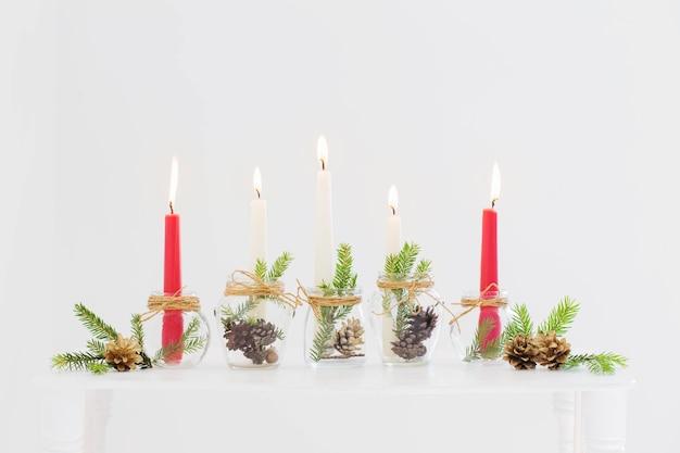 Decorazioni natalizie per la casa con candele accese in interni bianchi