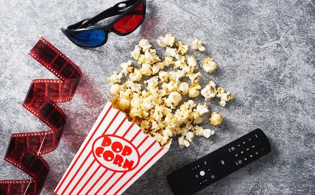 Home cinema popcorn al caramello in bicchieri di carta occhiali 3d e telecomando tv su loft backgroundflim