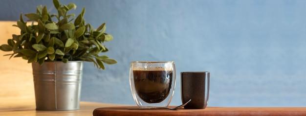 Tazza di caffè domestica sulla tavola di legno con lo spazio della copia alla retro caffetteria.