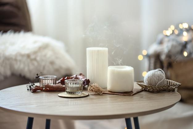 Composizione domestica in stile scandinavo con candele su sfondo sfocato con bokeh.