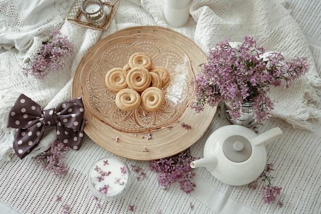Composizione casa con fiori primaverili, latte e biscotti a letto