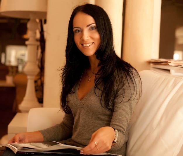 Concetto di casa - giovane donna sorridente che legge la rivista a casa?