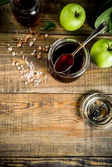Salsa al caramello salata scura classica fatta in casa, con mele verdi, fondo in legno e blu scuro,