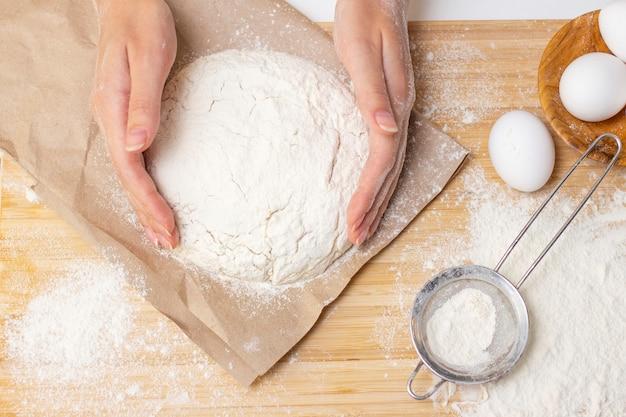 Concetto di cucina casalinga. le mani femminili preparano la pasta fatta in casa su una tavola di legno infarinata. avvicinamento.