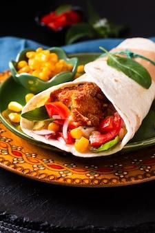 Concetto di cucina casalinga panino alla tortilla burrito di pollo fritto fatto in casa biologico sulla piastra a colori e lo spazio nero della copia