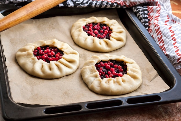 Cucina casalinga. galetts dolci con bacche di sambuco e mirtilli rossi sulla teglia pronta per la cottura