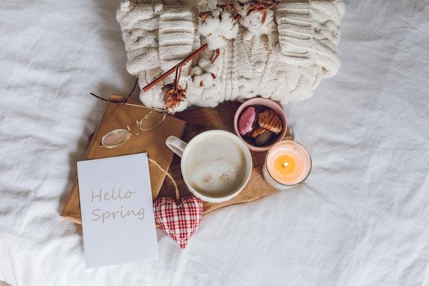 Arredamento accogliente per la casa e carta con il messaggio: hello spring. una tazza di cappuccino, biscotti, una candela sul letto.