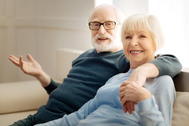 Giornata a casa. femmina abbastanza bionda che esprime positività mentre è seduto vicino al suo uomo e riposando a casa