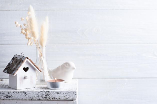 Decorazioni per la casa in stile scandinavo con fiori secchi di erba di pampa su fondo rustico in stile monocromatico. candele profumate e birdhouse con copia spazio