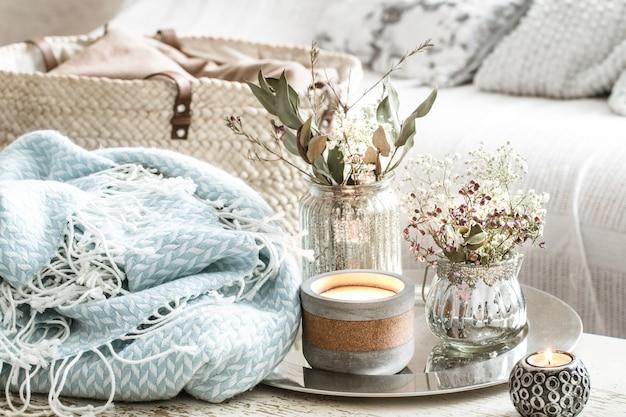 Decorazioni domestiche all'interno. una coperta turchese e un cesto di vimini con un vaso di fiori e candele