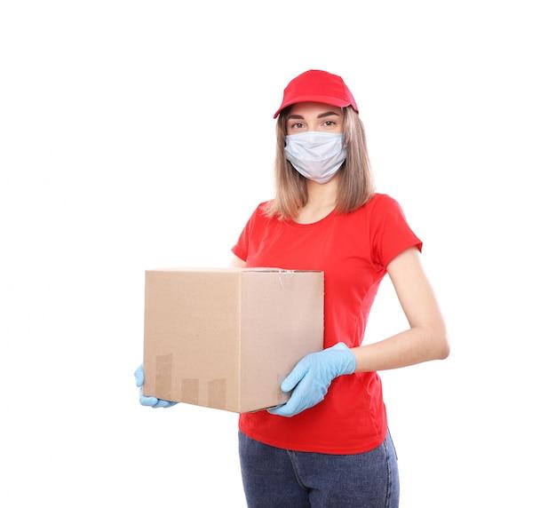 Consegna a domicilio, ordine online. corriere femminile in una maschera medica e guanti di gomma con una scatola, con un pacco in mano. consegna del cibo durante la pandemia di quarantena del coronavirus