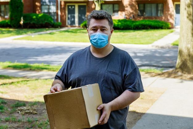 Consegna a domicilio, ordina online un uomo con una mascherina medica con una scatola, un pacco tra le mani, consegna di cibo durante la quarantena della pandemia di coronavirus.