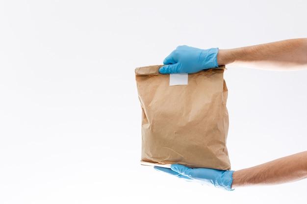Consegna a domicilio, ordine online. un uomo in uniforme, una maschera medica e guanti di gomma con una scatola, un pacco tra le mani. cibo e consegne a domicilio durante la quarantena della pandemia di coronavirus