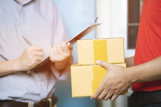 Consegna a domicilio, ordine online. un uomo in uniforme, una mascherina medica e guanti di gomma con una scatola
