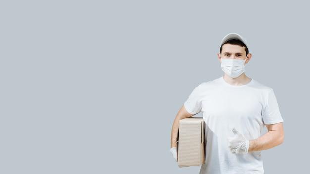 Il lavoratore di consegna a domicilio in guanti di maschere facciali tiene una scatola di cartone vuota